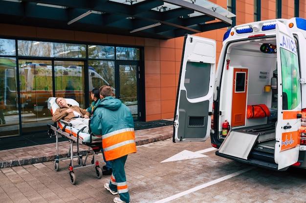Équipe sérieuse et professionnelle de médecins dans l'ambulance se déplaçant sur un patient à l'hôpital lors d'une situation d'urgence.