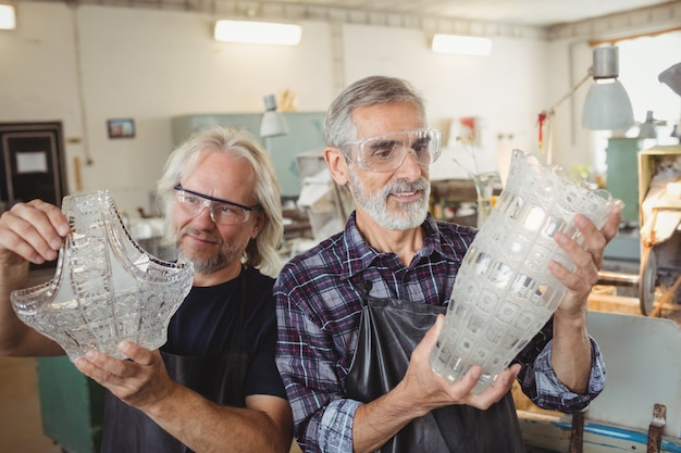 Équipe de souffleurs de verre examinant la verrerie