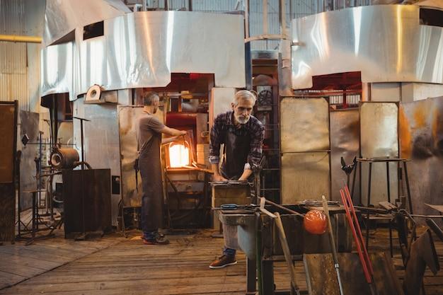 Équipe de souffleurs de verre façonnant un verre sur le chalumeau