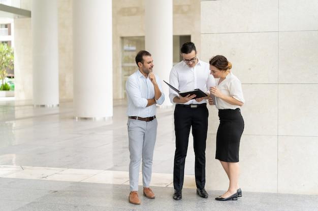 Équipe souriante examinant les documents avant la réunion