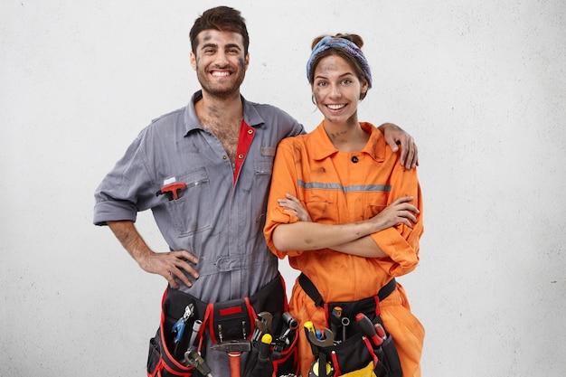 Une équipe souriante de techniciens se tient ensemble, heureux
