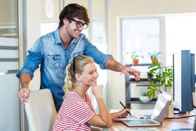Équipe souriante travaillant avec numériseur et ordinateur portable