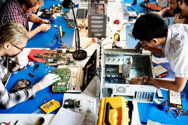 Équipe de techniciens en électronique travaillant sur des pièces d'ordinateur