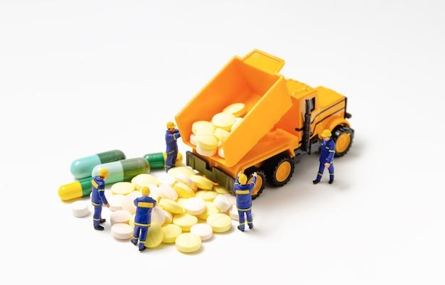Équipe de techniciens en miniature avec un camion remorque à benne basculante