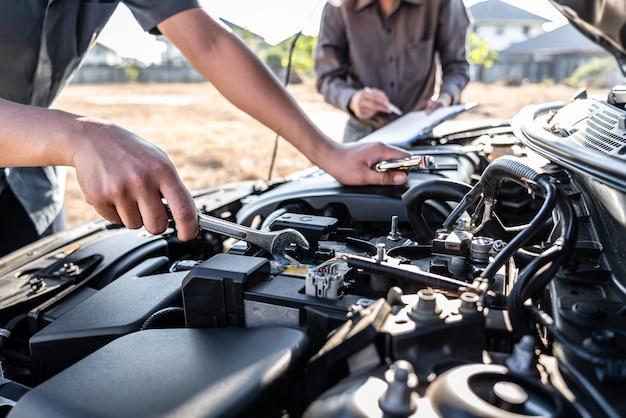 Équipe de techniciens travaillant sur un mécanicien automobile pour effectuer des réparations et des entretiens automobiles