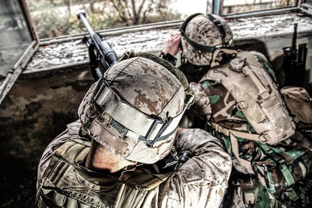 Une équipe de tireurs d'élite des marines armés d'un fusil de sniper anti-matériel de gros calibre se cachant dans un bâtiment urbain en ruine, tirant sur des cibles ennemies à distance d'un abri, assis dans une embuscade. fusillade militaire en ville