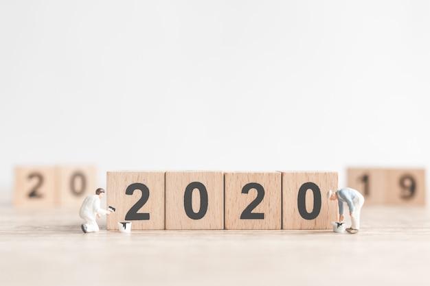 Équipe de travailleur miniature peint le numéro 2020 et enlève le numéro 2019