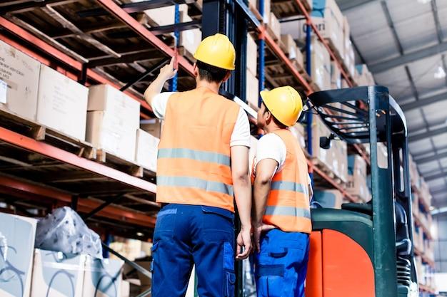 Équipe de travailleurs faisant l'inventaire dans l'entrepôt logistique