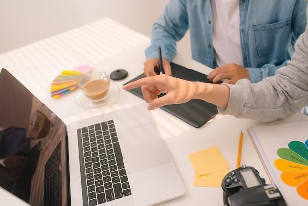 Équipe web designer travaillant à dessiner quelque chose sur un ordinateur graphique au bureau ou en studio