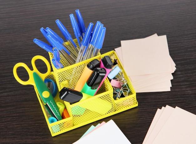 Équipement de bureau dans un support fixe jaune sur une table en bois foncé