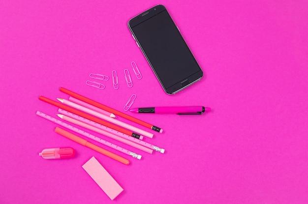 L'équipement de bureau rose et un téléphone mobile noir sont allongés sur rose isolé