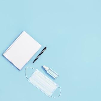 Équipement d'éducation et de protection individuelle. masque médical pour le visage, désinfectant pour les mains, cahier, stylo.