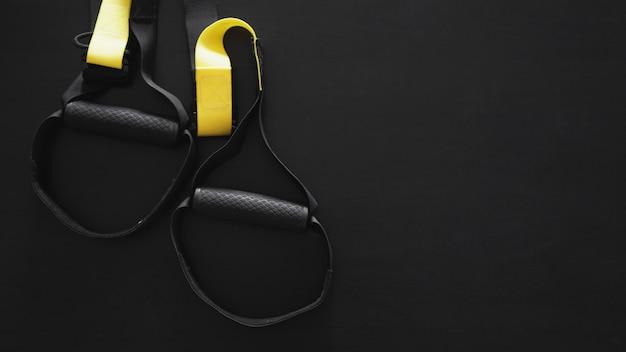 Équipement d'entraînement fonctionnel à sangle noire et jaune sur fond gris. accessoires sportifs. articles d'entraînement de fitness et de gym pour la santé. bannière trx