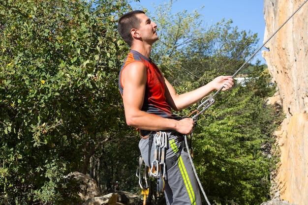 Équipement d'escalade sur un grimpeur masculin : chaussures de roche, corde, dégaine, dispositif de sécurité, harnais. tourisme sportif de montagne, mode de vie actif, sports extrêmes