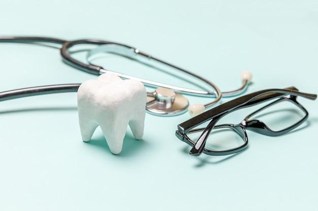 L'équipement de médecine stéthoscope lunettes dent saine blanc isolé sur fond bleu pastel