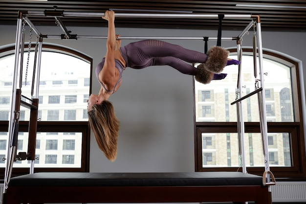 Équipement moderne réformateur cadilac pour pilates dans la salle de sport, concept de santé et de rééducation, l'instructeur effectue des exercices sur le réformateur pour corriger le système musculo-squelettique.