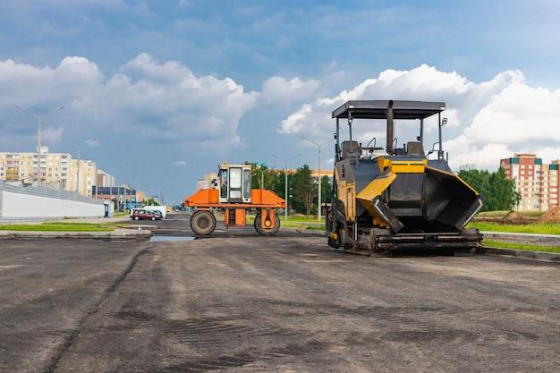 Équipement de pavage d'asphalte. finisseur d'asphalte et rouleau vibrant lourd. construction de nouvelles routes et carrefours routiers. machines industrielles de construction lourde.