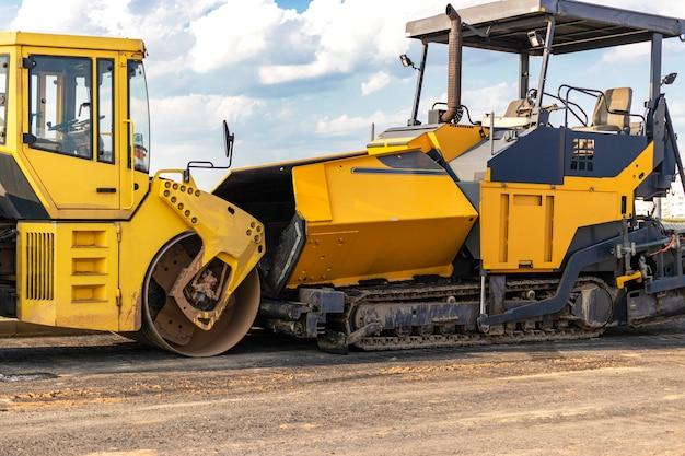 Équipement de pavage d'asphalte. finisseur d'asphalte et rouleau vibrant lourd.