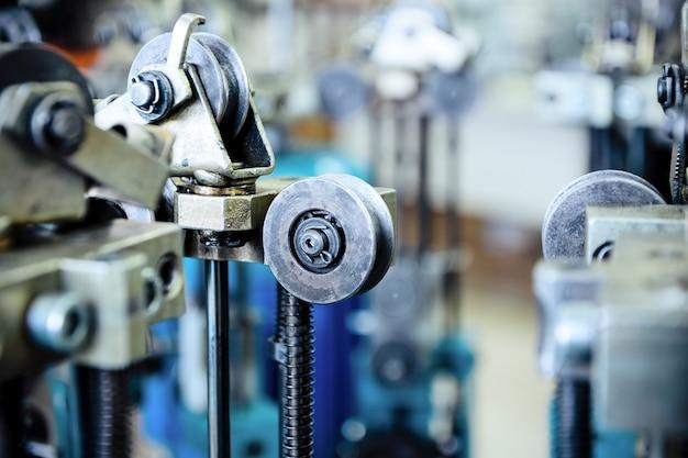 Équipement pour faire des tresses à partir de fil métallique. mise au point sélective. éléments du mécanisme de la machine à tresser. rouleaux de gros plan, roues, éléments de guidage.