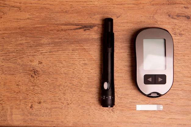 Équipement pour mesurer la glycémie sur table en bois.