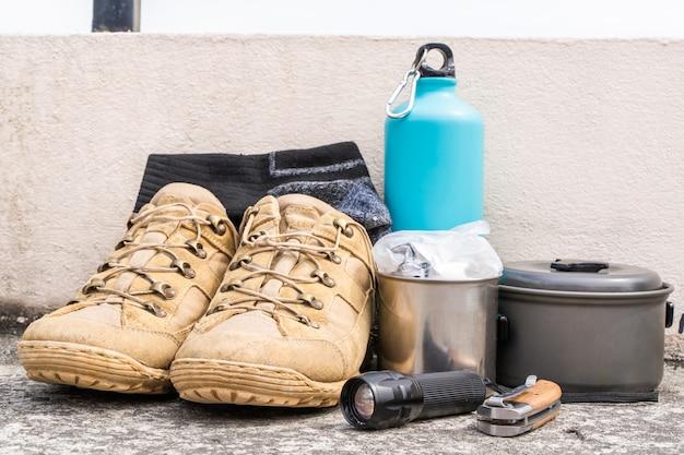 Équipement de randonnée ou de randonnée - bottes, chaussettes, couteau pliant, brûleur à gaz, gourde, marmite et lampe de poche. concept d'activité de plein air. nature morte gros plan photo.