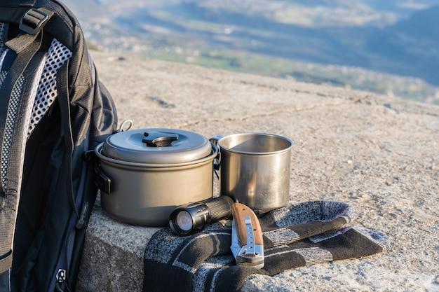 Équipement de randonnée ou de randonnée sur une clôture en béton. sac à dos, chaussettes, tasse en métal, marmite, couteau pliant et lampe de poche. concept d'activité de plein air.