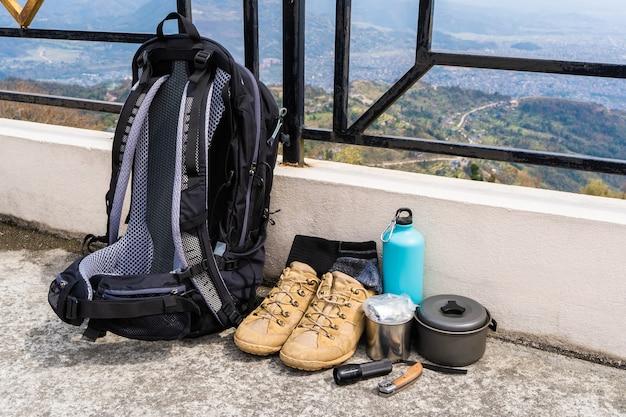 Équipement de randonnée ou de randonnée - sac à dos, bottes, chaussettes, couteau pliant, brûleur à gaz, gourde, bouilloire et lampe de poche. concept d'activité de plein air. nature morte gros plan photo.