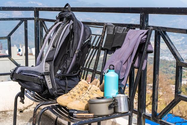 Équipement de randonnée ou de randonnée - sac à dos, bottes, chaussettes, pantalon, couteau pliant, gourde, bouilloire et lampe de poche. concept d'activité de plein air. nature morte gros plan photo.