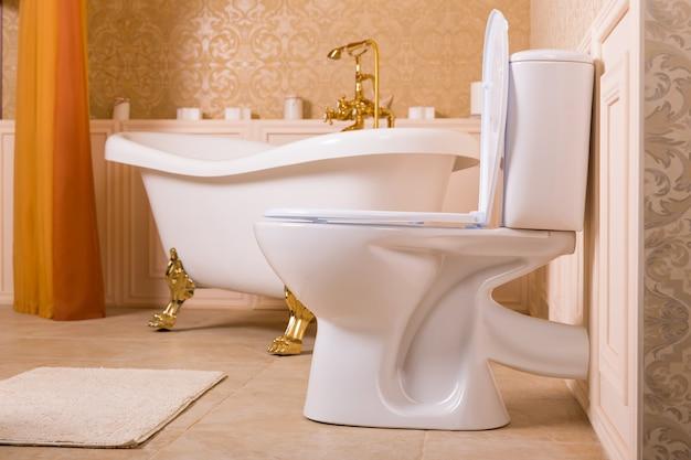 Équipement sanitaire de luxe avec éléments en or. bain riche avec des roll-tops dorés en forme de pattes d'animaux, robinet doré et toilettes dans la salle de bain.