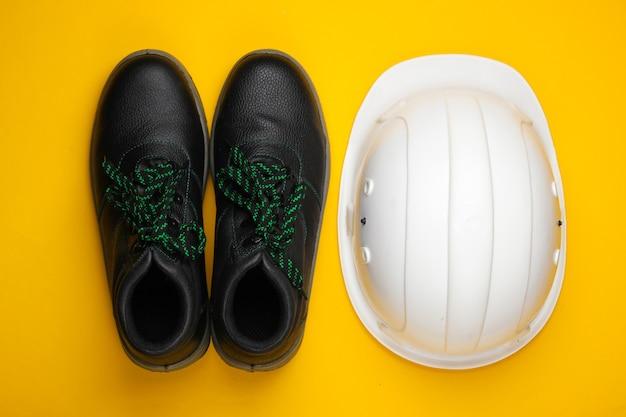 Équipement de sécurité casque de construction, chaussures de travail en cuir sur fond jaune. vue de dessus
