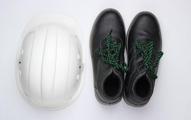 Équipement de sécurité sur fond blanc. casque de construction, chaussures en cuir de travail sur fond blanc. vue de dessus