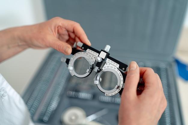 Équipement de soins de la vue. lunettes de test ophtalmologique dans les mains. mise au point sélective.