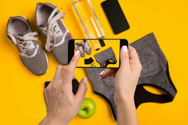 Équipement de sport photographiant sur téléphone portable. écran de smartphone avec image d'outils de fitness. conçu pour les réseaux sociaux
