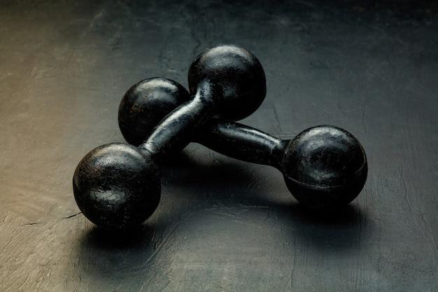 Équipement de sport professionnel isolé sur noir. poids de gymnastique noirs.