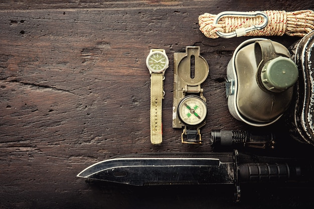 Equipement tactique militaire pour le départ. assortiment de survie, équipement de randonnée sur fond en bois