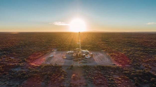 Équipement de traction dans le champ pétrolifère au coucher du soleil