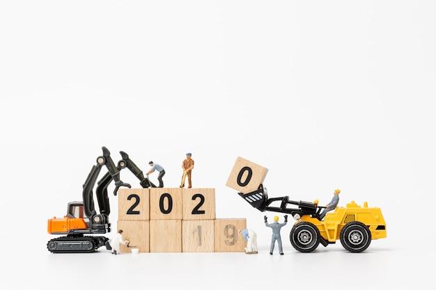 Les équipes de travailleurs créent un bloc en bois avec le numéro 2020
