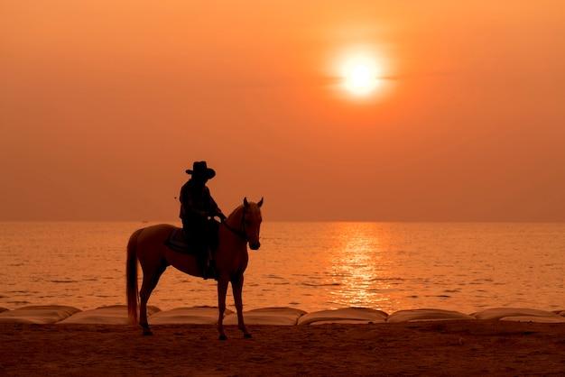 Équitation sur la plage au coucher du soleil