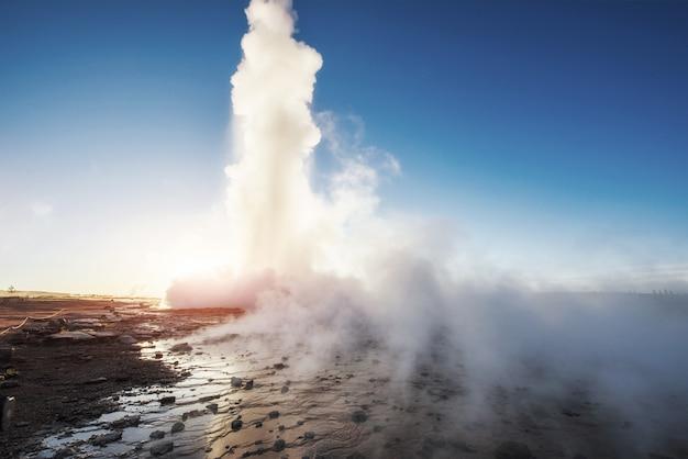 Eruption du geyser de strokkur en islande. des couleurs fantastiques brillent à travers la vapeur. beaux nuages roses dans un ciel bleu