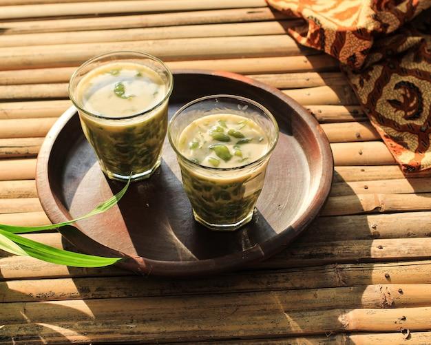 Es cendol ou dawet est un dessert glacé traditionnel indonésien à base de farine de riz, de sucre de palme, de lait de coco et de feuille de panda servi dans un verre sur une table en bambou. populaire pendant le jeûne du ramadan.