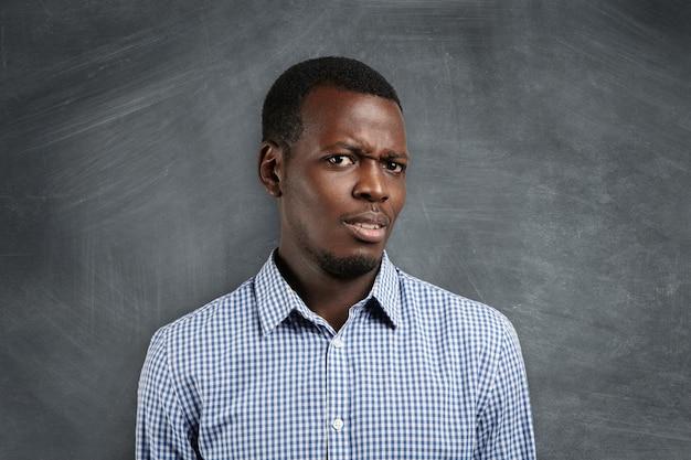 Es-tu sérieux? irrité jeune enseignant ou étudiant à la peau sombre vêtu d'une chemise à carreaux, l'air insatisfait et surpris, debout contre un tableau noir avec un espace de copie pour votre publicité