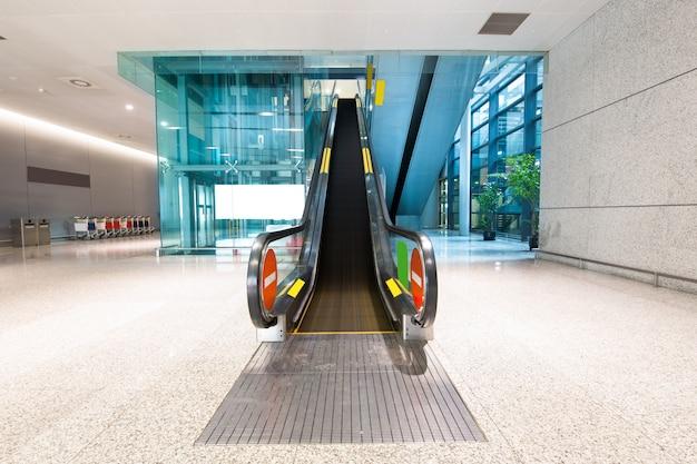 Escalator d'immeuble de bureaux moderne, images aux tons bleus.