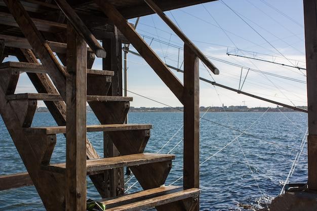 Escalier en bois un restaurant rustique sur un barrage dans la mer en italie.