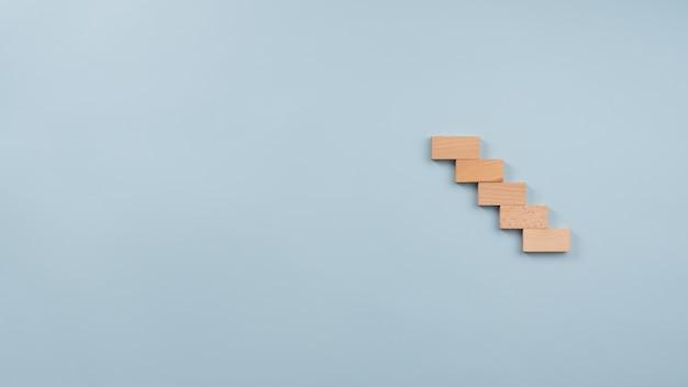 Escalier composé de cinq chevilles en bois dans une image conceptuelle.