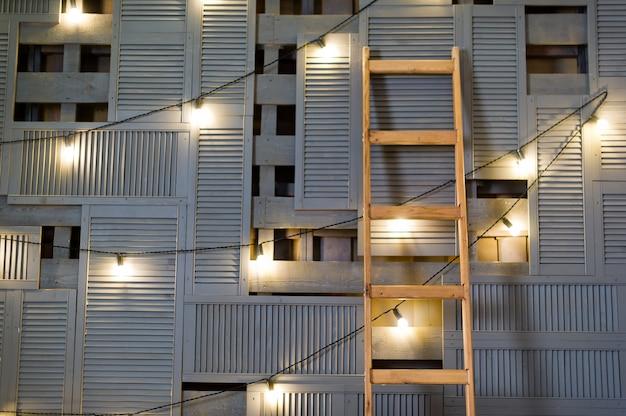 Escalier debout contre un mur en bois, guirlande rétro.