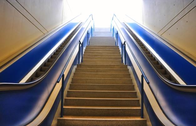 Escalier et deux escaliers mécaniques sous les lumières dans un immeuble