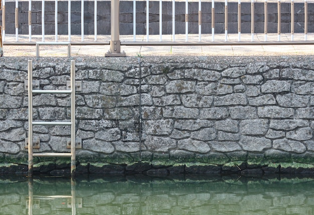 Un escalier d'échelle emergrncy sur le vieux mur de pierre près de la rivière.