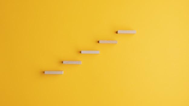 Escalier fait de chevilles en bois sur fond jaune vif. avec espace copie.