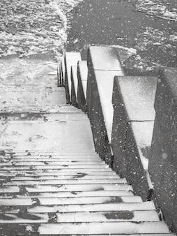 Escalier en granit menant à la rivière gelée. dérive de glace sur la rivière.