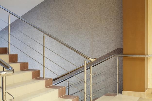 Escalier marron avec garde-corps en métal, mur gris
